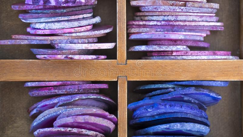 Interesting color patterns created by sectioned geodes pilled neatly in a wooden box stock photo