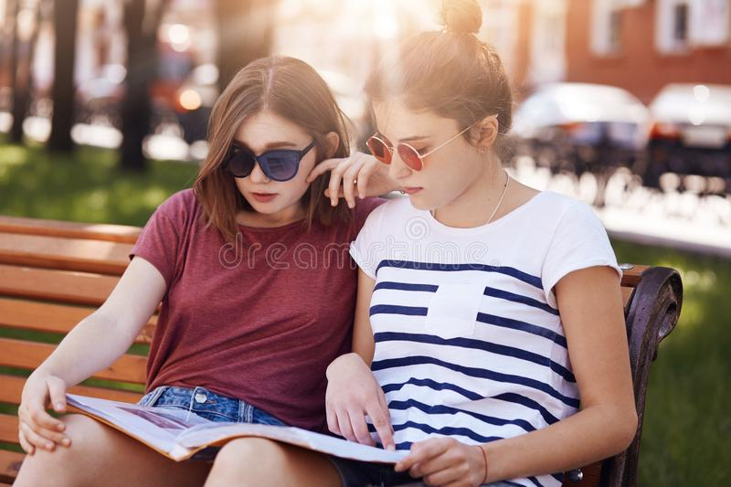 Horizontal shot of serious female teenagers look attentively at fashion magazine, read interesting article about famous model brea stock image