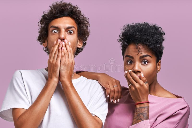 Horizontal shot of shocked African American young female and male look with scared frightened expressions at camera stock photos