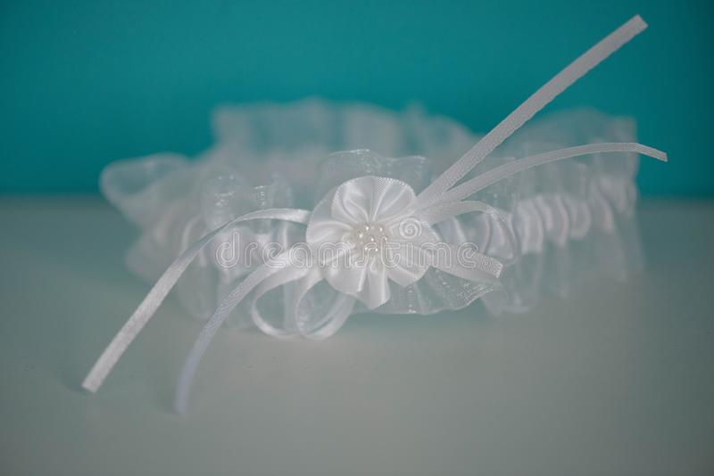 Silky white garter with flower detail and white pearly beads. Horizontal shot of silky white garter with flower detail and white pearly beads, tasteful accessory stock images