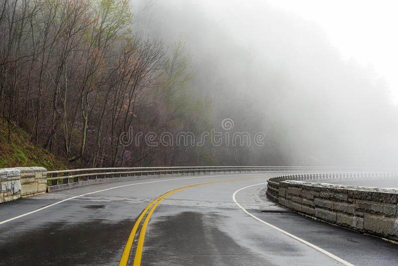 Smoky Mountain Road Disappears Into Fog With Copy Space. Horizontal shot of a Smoky Mountain road disappearing into fog with copy space stock image