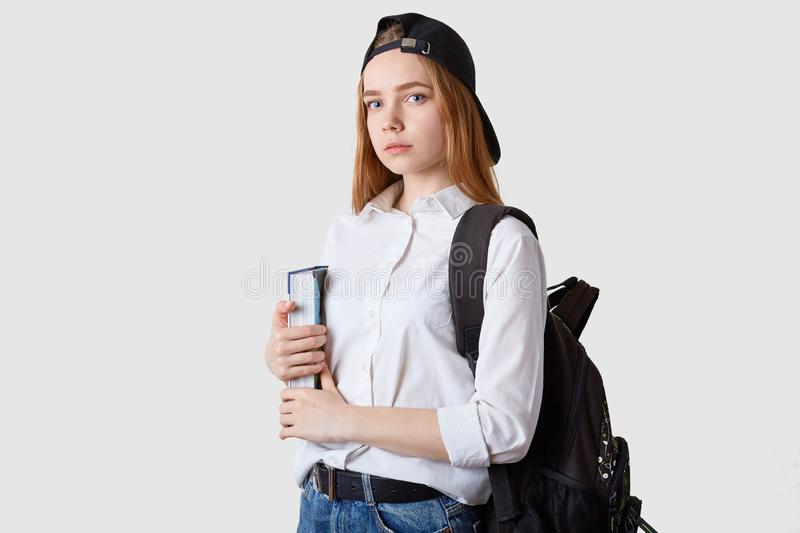 Horizontal shot of student girl standing isolated over white background, holding paper folders in hands, wearing blouse, black cap. And backpack, looking at royalty free stock photos