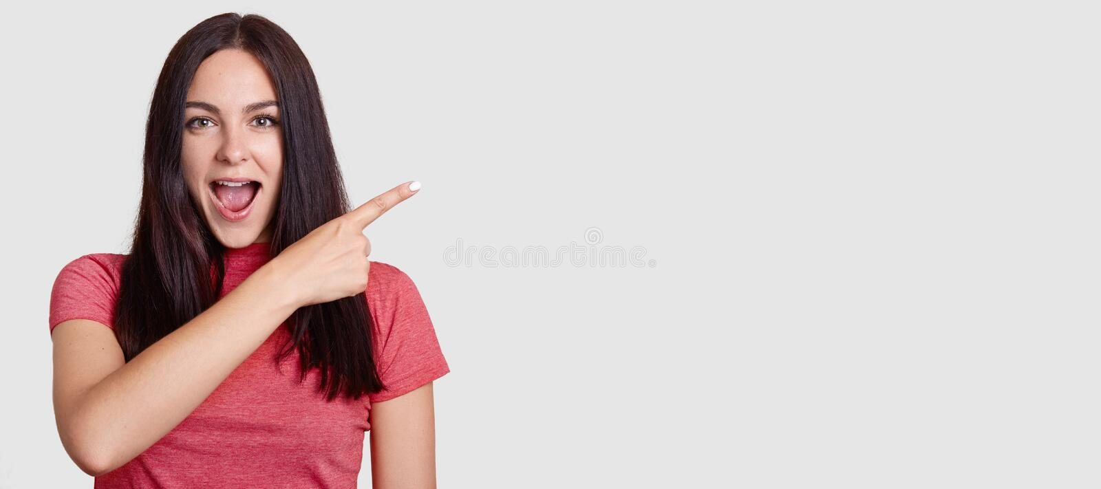 Horizontal shot of surprised brunette woman with dark hair, dressed in pink t shirt, points with index finger asie, shows free spa. Ce for your promotion stock photography