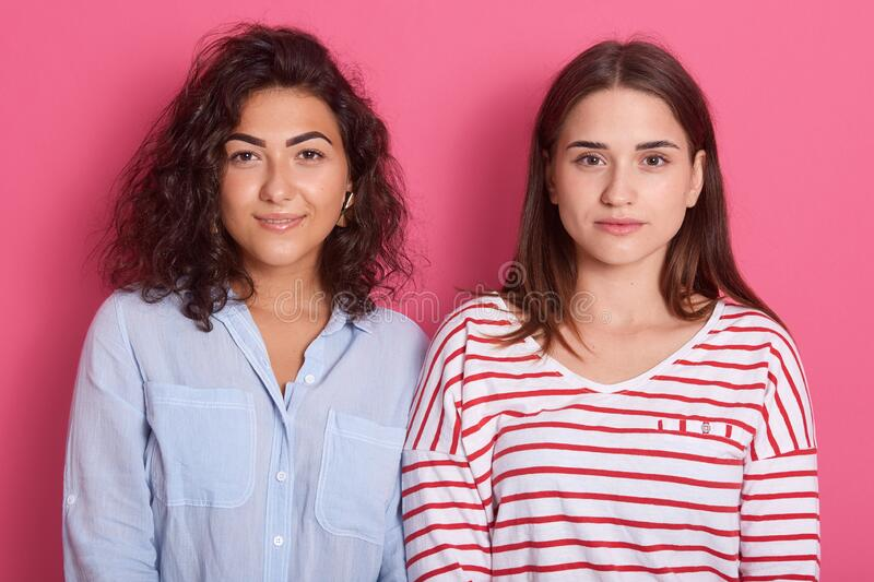 Horizontal shot of two females with calm face. Women standing isolated over pink stidio background, one lady wearing blue blouse, stock photography
