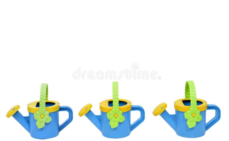 Watering Pail Border. Horizontal shot of a watering pail border across the bottom consisting of three blue and yellow watering cans with green handles on a white royalty free stock image