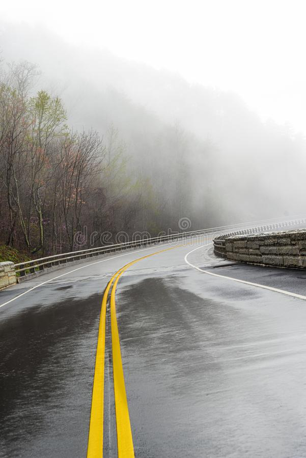 Curving Smoky Mountain Road Disappears Into Fog With Copy Space. Horizontal shot of a wet curving Smoky Mountain road disappearing into fog with copy space stock photos