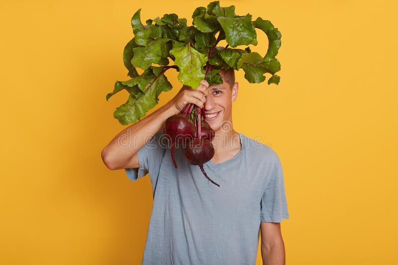 Horizontal shot of young handsome male holding bunch of beets in hand, hiding behind fresh vegetables, posing in casual outfit, fotografia stock libera da diritti