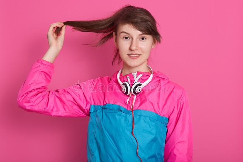 Horizontal shot of young pleased dark haired woman touching her brown long hair with raised hand while posing over pink studio stock image