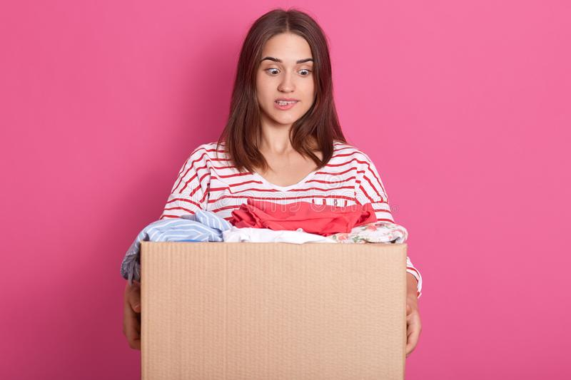 Horizontal shot of young volunteer stands with carton box full of donated clothes, adorable woman looking at clothes with scared royalty free stock photography