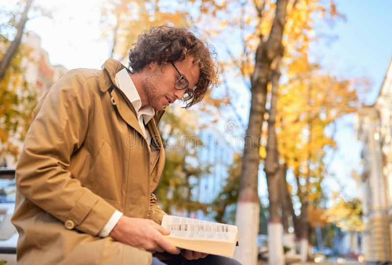 Horizontal side view image of trendy handsome young man reading book outdoors. College male student carrying books in campus in. Horizontal e view image of royalty free stock image