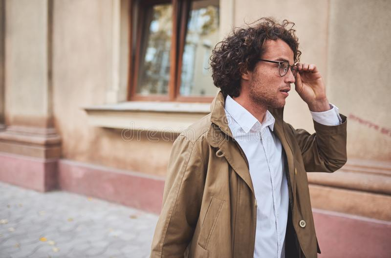 Horizontal side view potrait of young businessman with glasses posing outdoors. College male student in autumn street. Smart guy royalty free stock photography