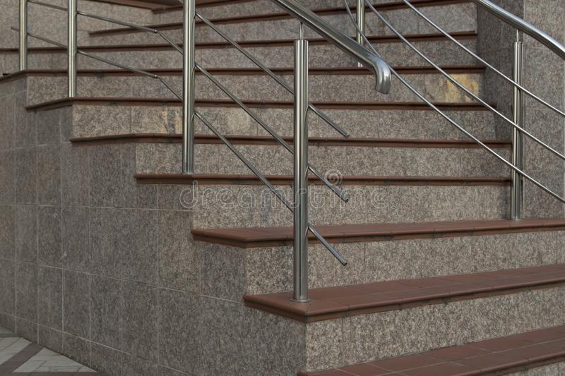 Horizontal steps made of brown ceramic tiles turning stairs made of gray marble tiles leading to the entrance to office. Horizontal steps made of brown ceramic stock images