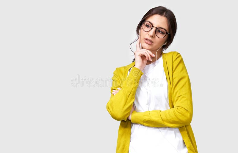 Horizontal studio portrait of pretty brunette woman in eyewear touching her chin and looking aside to the blank copy space. royalty free stock photos
