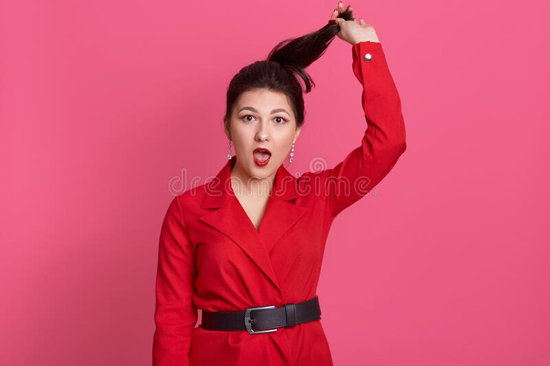 Horizontal studio shot of emotional charismatic brunette holding her ponytail with one hand, opening mouth widely, having shocked. Facial expression, wearing royalty free stock photography