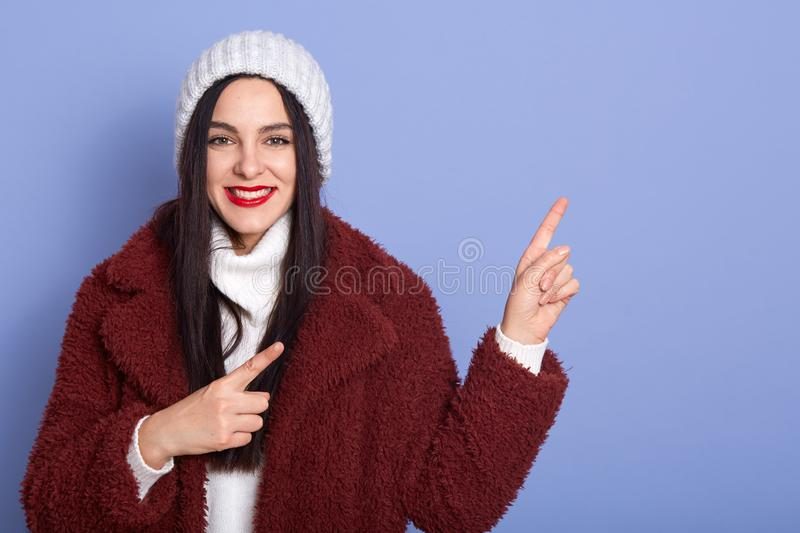 Horizontal studio shot of good looking pretty model making gestures, pointing with forefingers, looking directly at camera, royalty free stock image