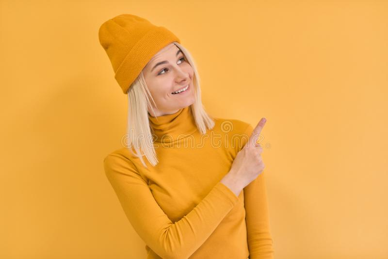 Horizontal studio shot of prettty young woman smiling and points with fore finger away, indicates copy space on blank wall, royalty free stock image