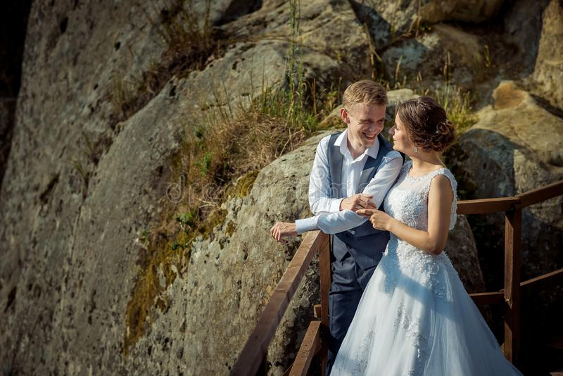Horizontal sunny portrait of the beautiful newlyweds smiling and holding hands at the background of the mountains. stock photos