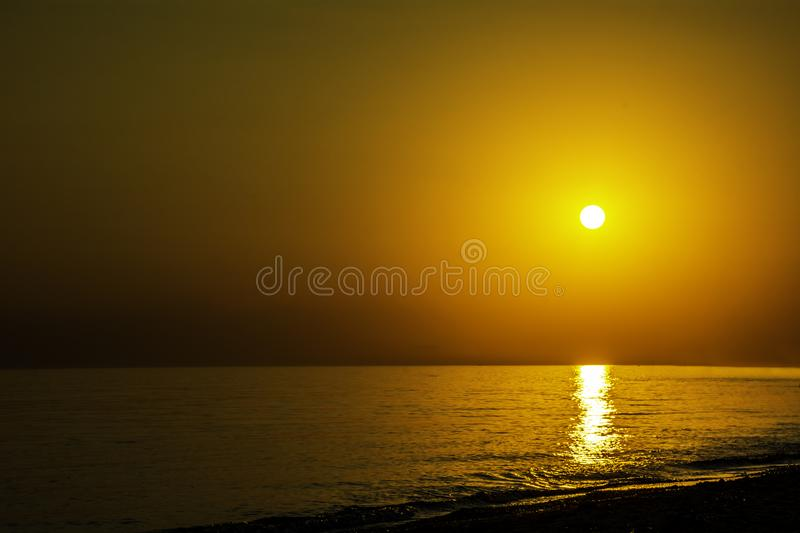 Horizontal sunset coastline calm sea with golden sun - Late afternoon on beach waterline with golden direct sunset calm sea ocean stock photos