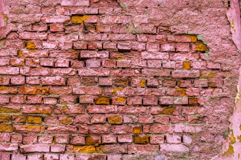 A horizontal texture of part of a old crashed brick wall in pink hue is on the photo. A beautiful horizontal texture of part of a old crashed brick wall in pink stock photography