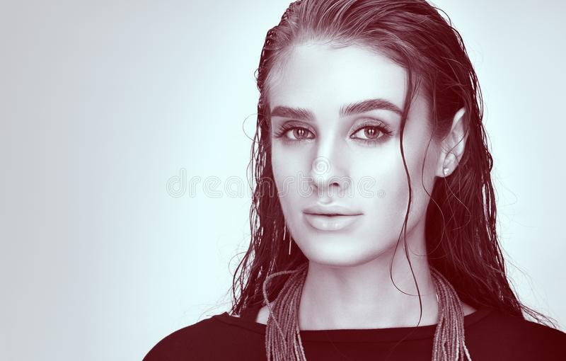 Horizontal toned portrait of young woman in black. Wet hair and professional makeup. Sensual look stock photography
