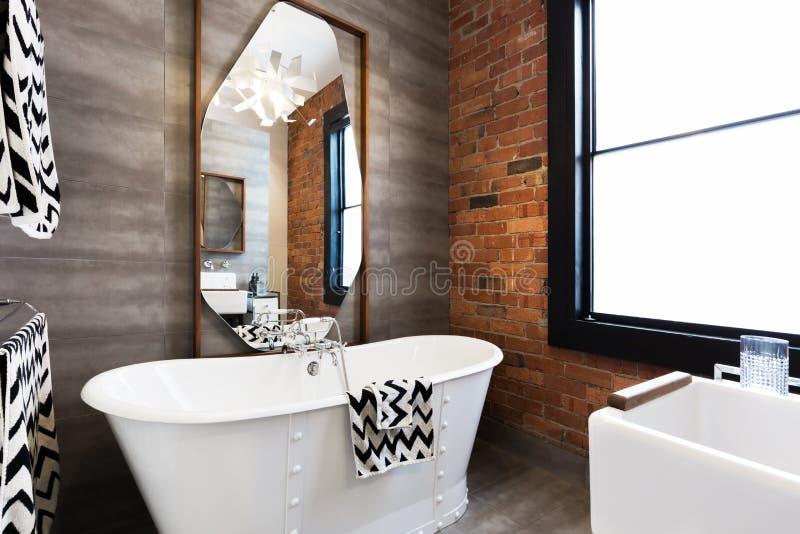 Horizontal version freestanding vintage style bath tub in renovated warehouse apartment. Horizontal version freestanding vintage style white bath tub in stock photo