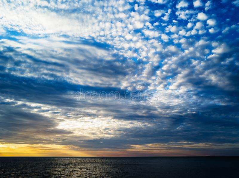 Horizontal vibrant ocean horizon cloudscape background backdrop. Nobody blank empty space sparse vivid bright color rich composition design concept element royalty free stock photo