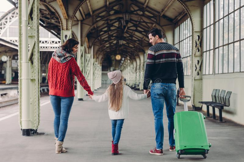 Horizontal view of affectionate parents and their dauhter keep hands together, going to have trip abroad, pose on railway station stock photo