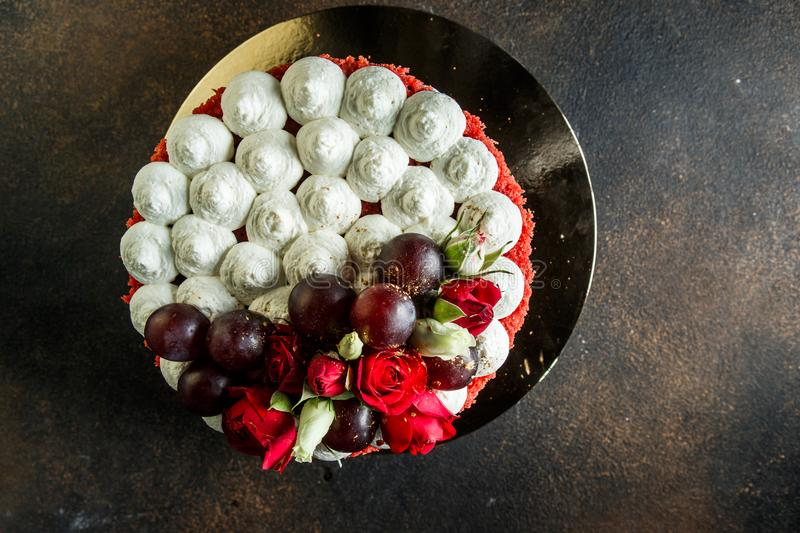 Horizontal view of cake decorated with bizet, grapes and roses. Horizontal top view of beautiful cake decorated with white bizet, grapes and roses stock image