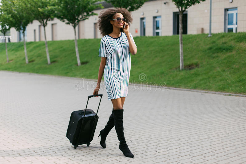 Horizontal view of the cheerful afro-american girl holding the luggage while talking using the mobile phone. royalty free stock photos