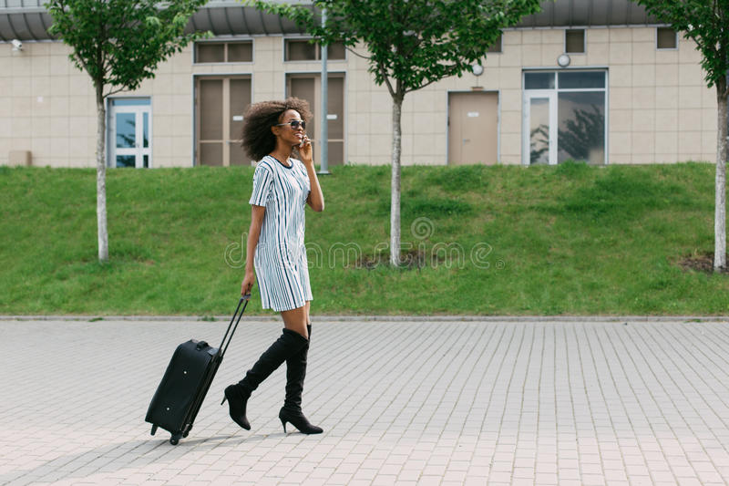 Horizontal view of the cheerful afro-american girl holding the luggage while talking via the mobile phone. Horizontal view of the cheerful afro-american girl royalty free stock images
