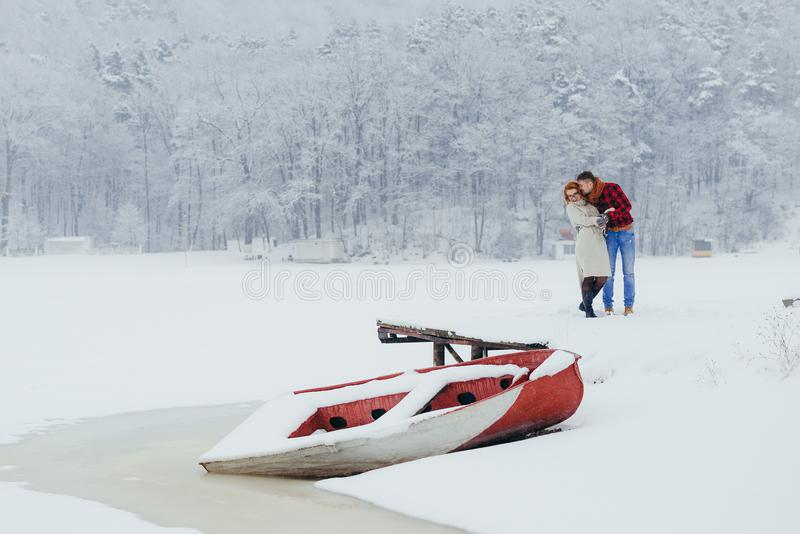 Horizontal view of the cheerful beautiful couple standing in the front of the snowy boat. The man is kissing his red stock image