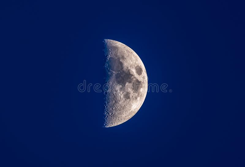 Horizontal view of a clear bright half moon in a blue night sky. Just before Vesak stock image