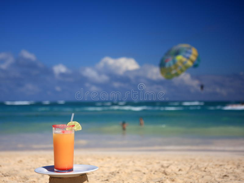 Horizontal view of cocktail on the beach. Orange cocktail with straw on the tropical beach stock photography