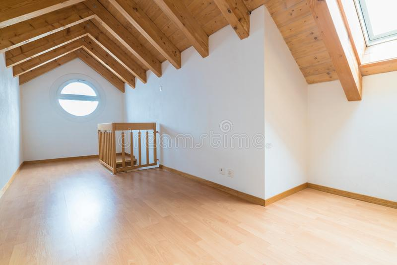 Empty spacious and bright attic in a refurbished apartment with wooden parquet floor and white walls and wooden gable roof stock photos