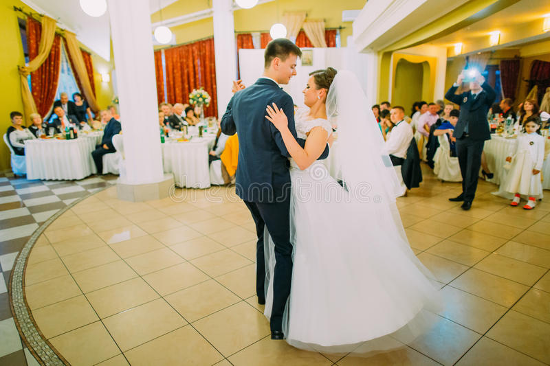 The horizontal view of the happy dancing newlywed couple in the restaurant. stock image