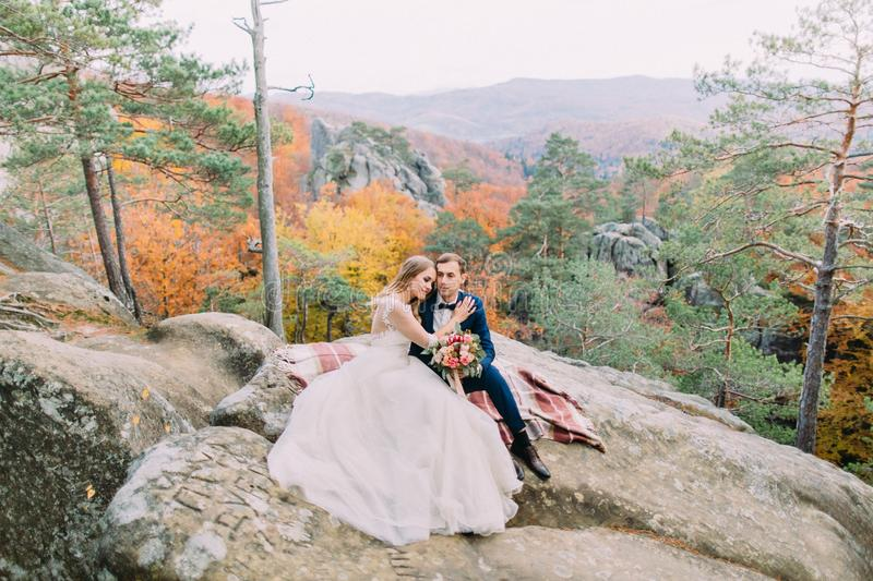 Horizontal view of the happy newlywed couple sitting on the knitted plaid on the rock. royalty free stock photo