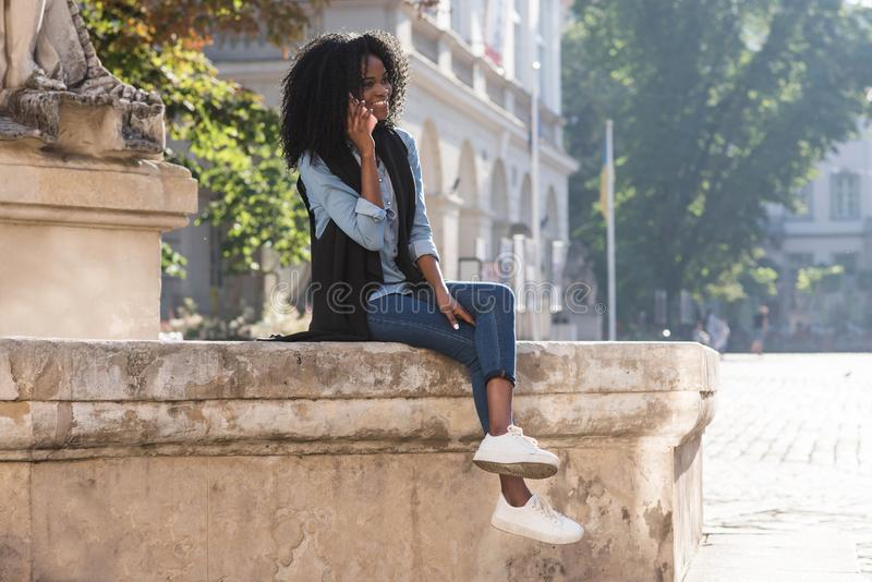 The horizontal view of the magnificent afro-american girl sitting on the fountain while talking via the mobile phone. royalty free stock images