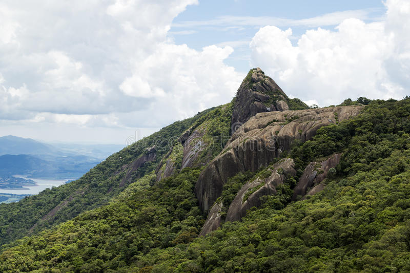 Horizontal view of a mountain rock face with some trees under a blue sky with white clouds - pico e serra do lopo royalty free stock image