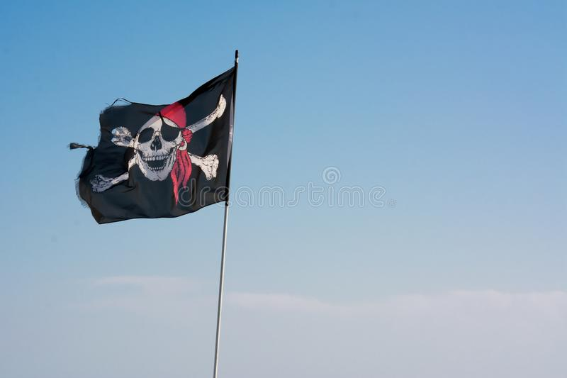 Horizontal View of The Pirates` Jolly Roger Flag on Blue Sky Bac. Kground in the Wind royalty free stock photos