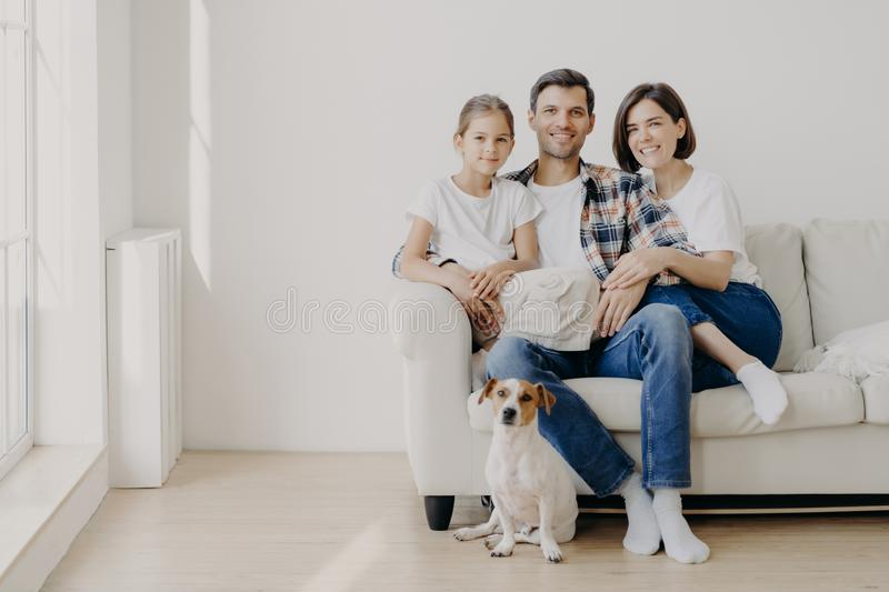 Horizontal view of three friendly family members and small pedigree dog pose at camera for making memorable photography. Dauther stock photography