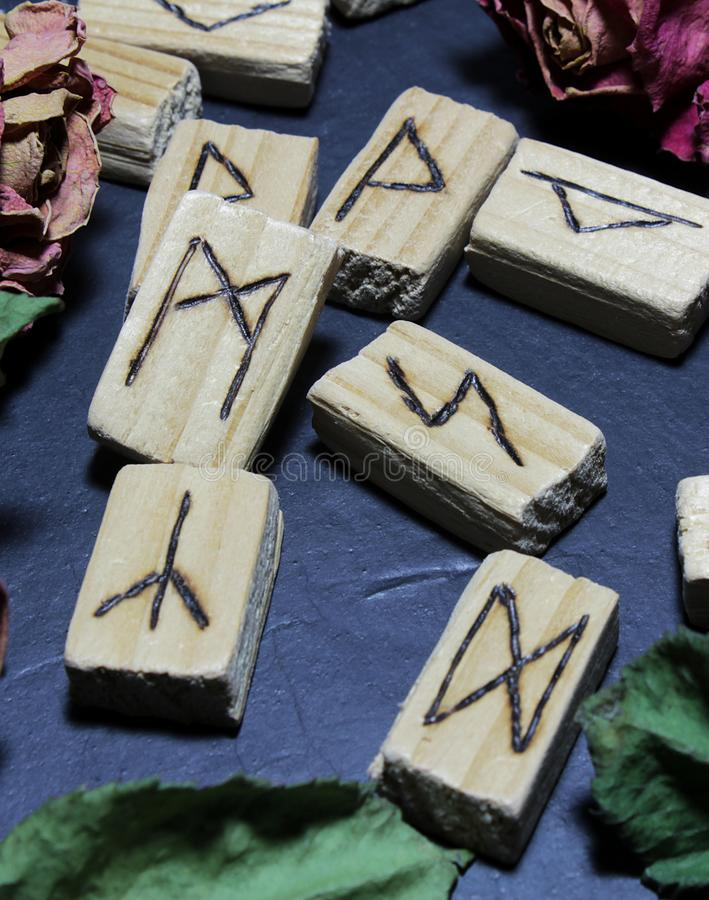 Horizontal view of wooden runes that lie on a dark stone background stock photography