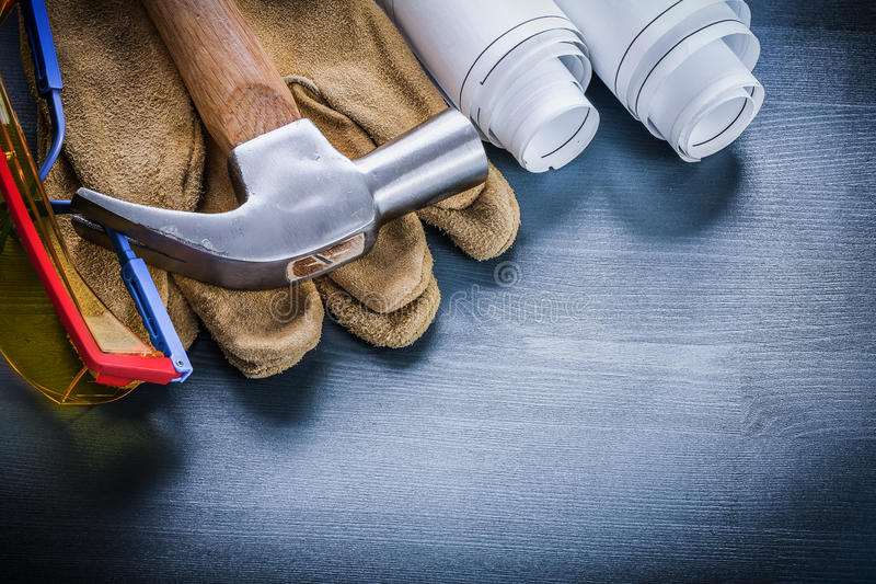 Horizontal view working gloves goggles hammer rolled blueprints.  royalty free stock image