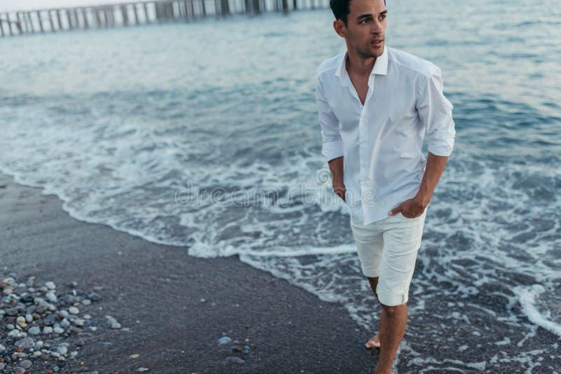 Horizontale aantrekkelijke bebouwde mens die witte overhemd en broek dragen stock fotografie