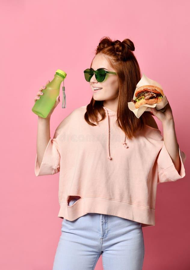 Horizontale Atelieraufnahme der recht jungen Frau, die einen Burger und ein Glas Soda hält stockfotografie