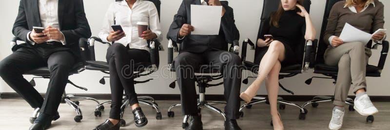 Horizontale beeld diverse kandidaten die in gesprek van de rij het wachtende baan zitten stock foto's