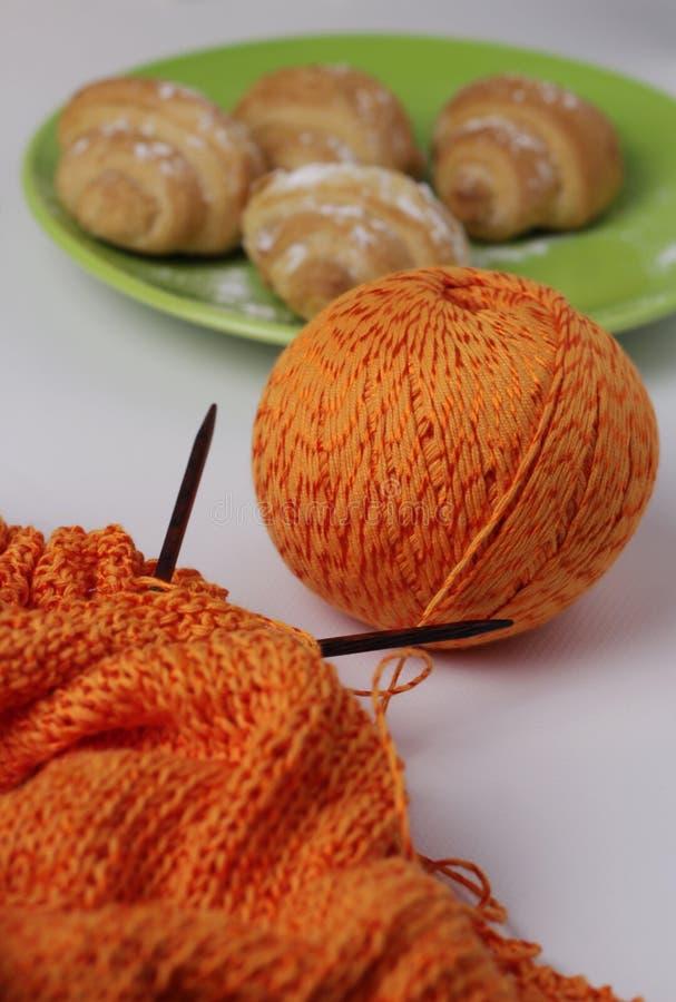 Horizontale foto van het het breien proces van oranje garen Erachter zijn croissants, dessert Onduidelijk beeldeffect stock fotografie