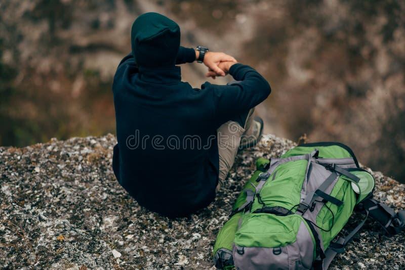 Horizontale hintere Ansicht geschossen vom jungen hübschen Wanderermann, der auf dem Felsen, entspannend und die schöne Naturansi lizenzfreies stockbild