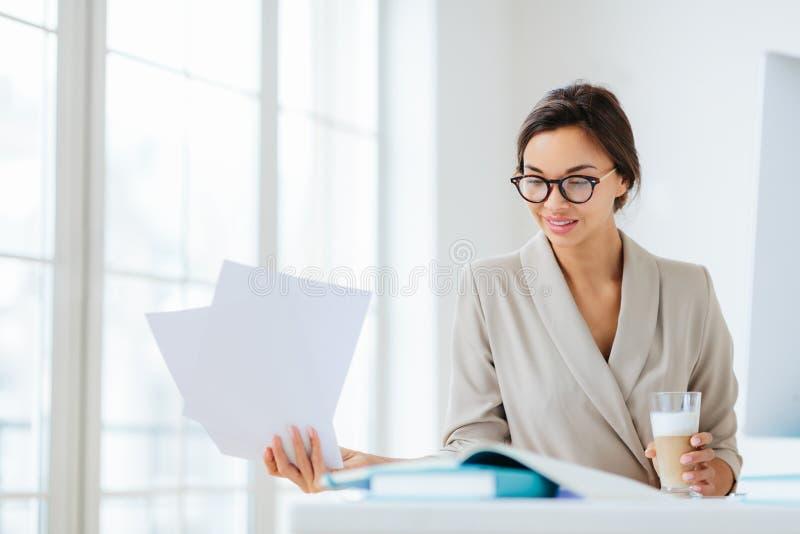 Horizontale kijk op zelfverzekerd brunette vrouwelijke arbeider in formele slijtage en optische bril kijkt door documentatie, dri stock afbeelding