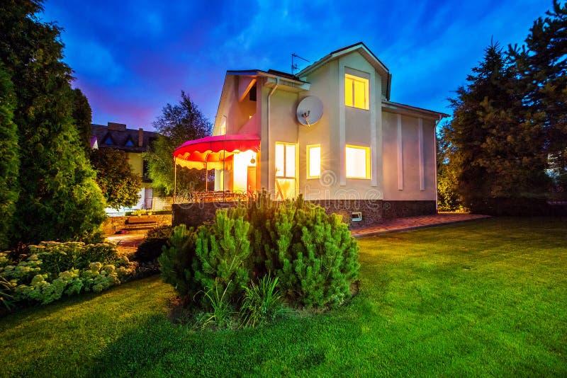Horizontale mening van eengezinswoning met terras Duisternis met verlichting Geel licht van vensters stock afbeelding