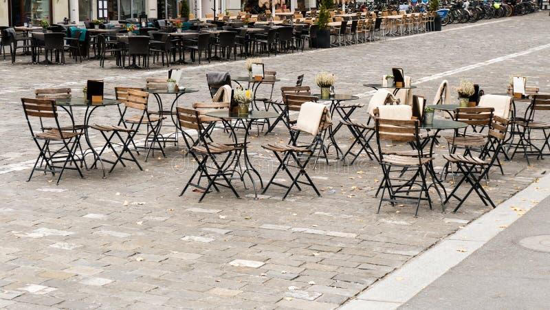 Horizontale mening van lege lijsten en stoelen in een openluchtrestaurant met een totale afwezigheid van klanten stock foto's